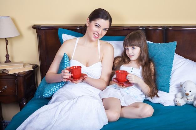 행복한 엄마와 딸이 재미 있고 컵을 들고 침대에서 쉬고 카메라를 보며 웃고 있습니다.