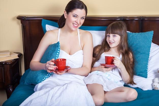 행복한 엄마와 딸은 재미 있고 컵을 들고 침대에서 쉬고, 이빨 미소로 카메라를 바라보고 있습니다.