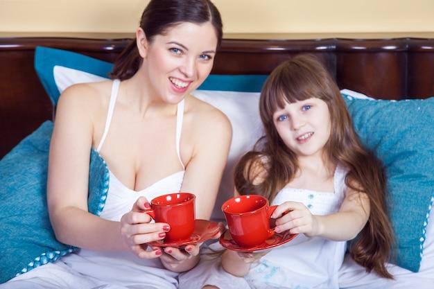 행복한 엄마와 딸이 재미 있고 컵을 들고 침대에서 쉬고 있다