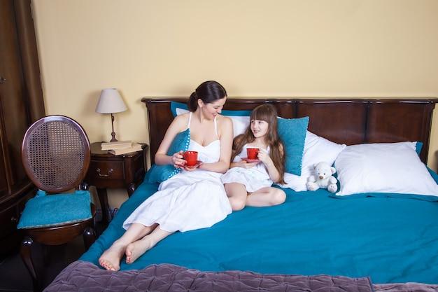 행복한 엄마와 딸이 재미 있고 컵을 들고 침대에서 쉬고,