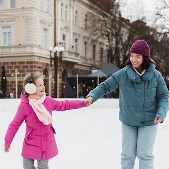 幸せな母と娘が手を繋いでいます。