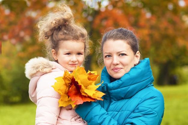 秋の公園で幸せな母と娘