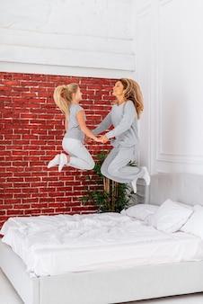행복 한 엄마와 딸 침대에서 점프