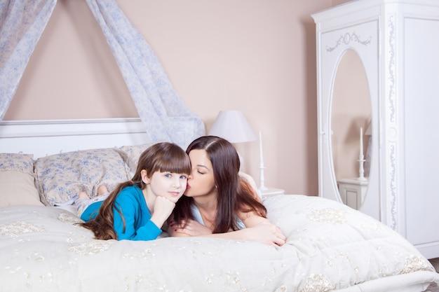 Счастливая мать и дочь лежали в постели, весело, улыбаясь и глядя в камеру. студийный снимок.