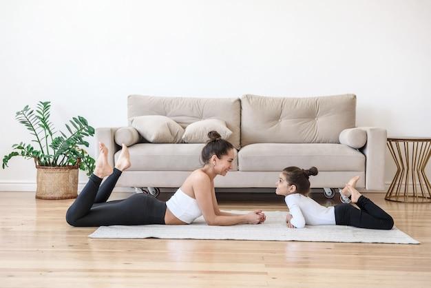 행복 한 엄마와 딸 작은 아이 소파 옆에 거실 바닥에 함께 누워 서로 미소