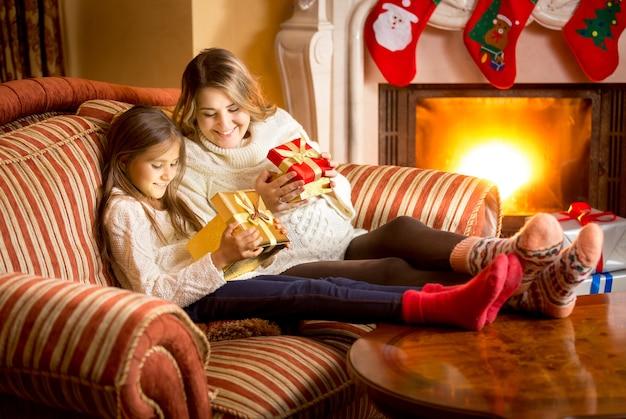 크리스마스 선물 상자 안을 보고 있는 행복한 엄마와 딸