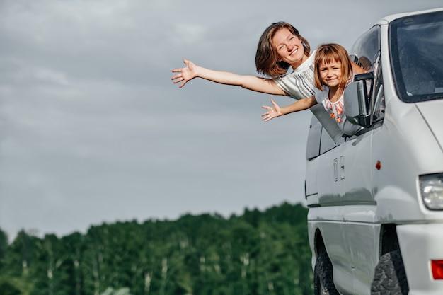 행복한 엄마와 딸이 창문에서 바라보고 여행을 즐기고 있습니다. 자동차로 여행하는 가족.
