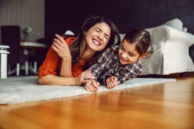 幸せな母と娘が家の床に横になって笑っています。