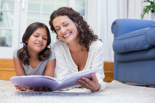 幸せな母と娘が床に横たわって本を読む