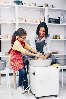 幸せな母と娘が糸車で粘土陶器を作っています。