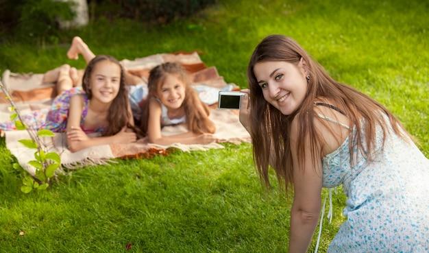Счастливая мать и дочь делают фотографии во время пикника в парке