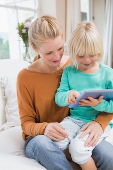 Счастливая мать и дочь на диване с помощью планшета