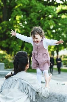 Счастливая мать и дочь, играя на улице
