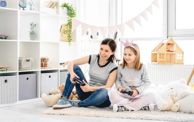 Счастливая мать и дочь, играя в видеоигры в детской комнате