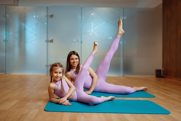 Счастливая мать и дочь позирует на циновках в тренажерном зале, тренировки йоги. мама и маленькая девочка в спортивной одежде, женщина с ребенком на совместной тренировке в спортивном клубе