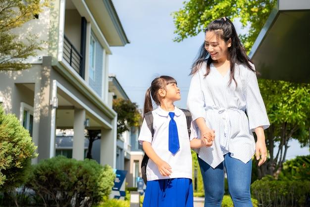幸せな母と娘の小学生が学校に歩いて