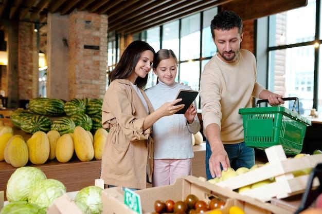 Счастливая мать и дочь читают точки списка покупок, стоя у фруктовой витрины в современном супермаркете
