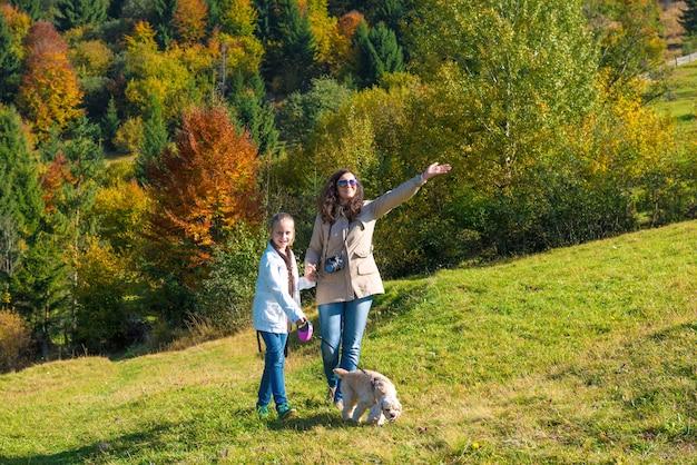 Счастливая мать и дочь отдыхают в осеннем лесу, мать указывая на что-то