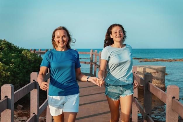 행복한 엄마와 딸이 바다로 보도를 달리고 있습니다. 웃고 있는 중년 여성과 10대 소녀가 손을 잡고 일몰, 3/4 길이 샷을 걷고 있습니다. 티셔츠 모형