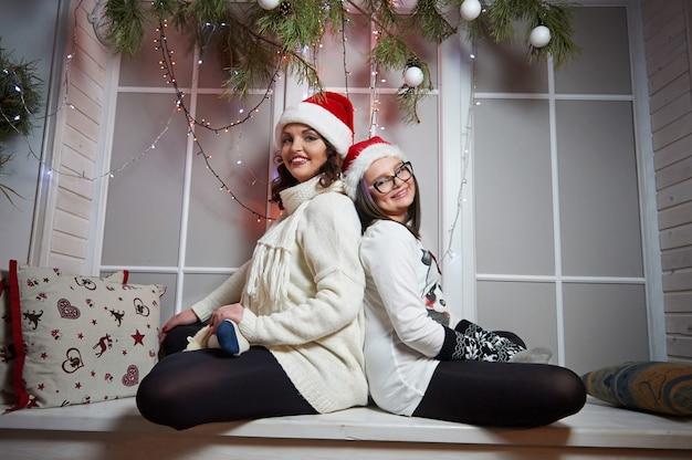 幸せな母と娘のクリスマスeの窓辺に座っています。