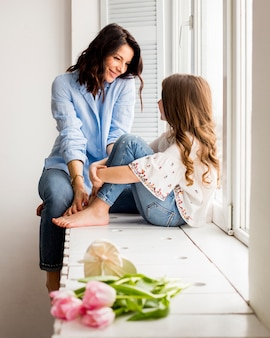 Счастливая мать и дочь, сидя на подоконнике