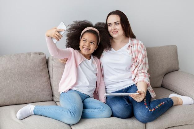 Счастливая мать и дочь, принимая селфи вместе