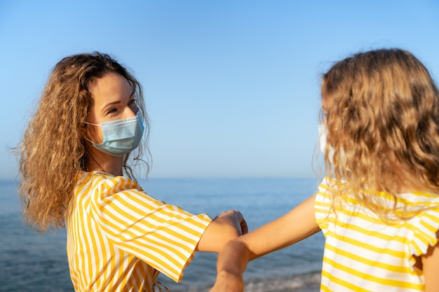 Счастливая мать и дочь в медицинской маске на открытом воздухе против голубого неба.