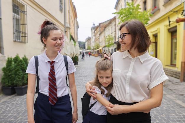 Счастливая мать и дочери идут в школу