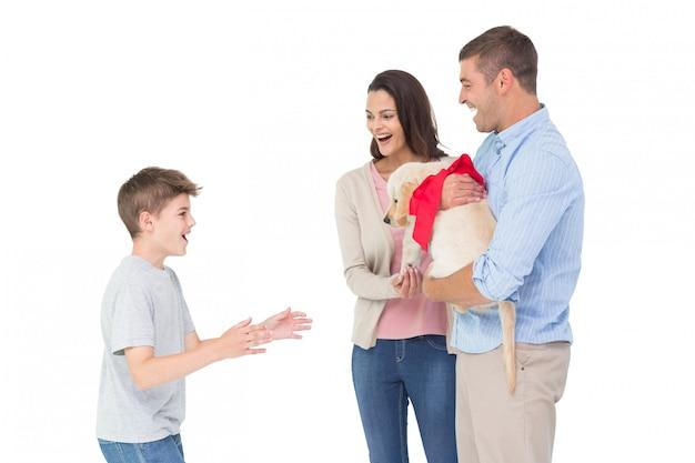白い背景の上に少年に贈り物をする幸せな母と父