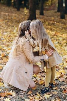 幸せな母と彼女の美しい娘は楽しんで、秋の公園を散歩します。