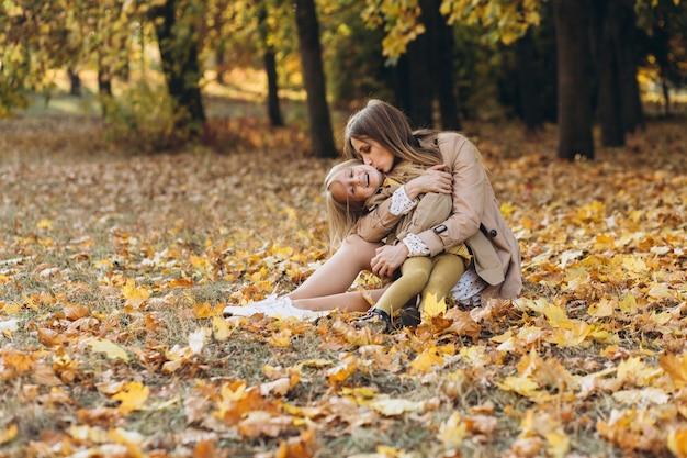 幸せな母と彼女の美しい娘は、秋の公園の黄色の葉の中で座って楽しんでいます。