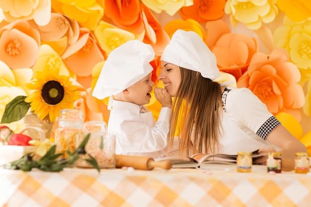 요리사의 형태로 행복한 엄마와 그녀의 아이가 축제 저녁 식사를 준비합니다