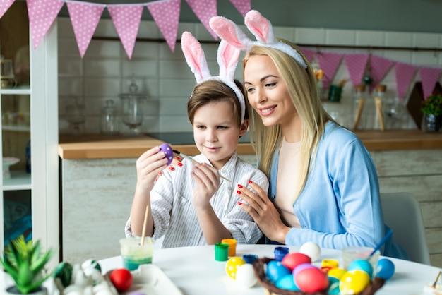 행복 한 어머니와 그녀의 귀여운 작은 아들 부활절 달걀을 함께 페인트. 부활절 개념