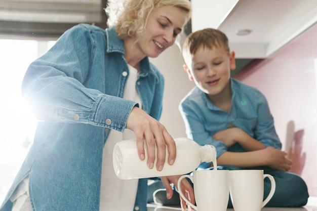 Счастливая мать и ее милый сын пьют молоко на кухне