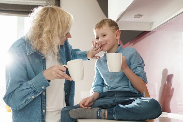 Счастливая мать и ее милый сын пьют чай на кухне