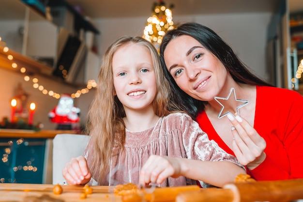 幸せな母と娘がキッチンでクリスマスクッキーを調理します