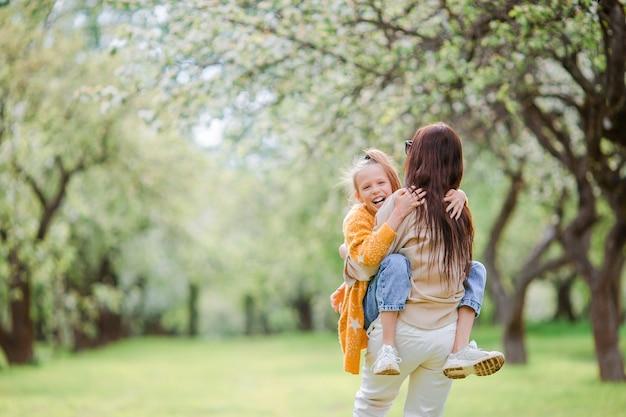 Счастливая мать и ее дочь веселятся на открытом воздухе в парке