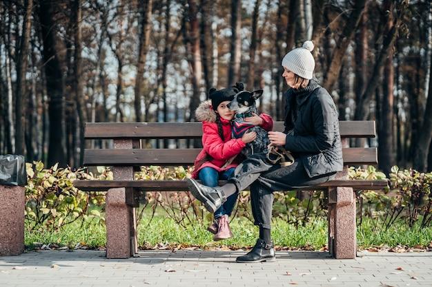 Счастливая мать и ее дочь с собакой отдыхает на скамейке