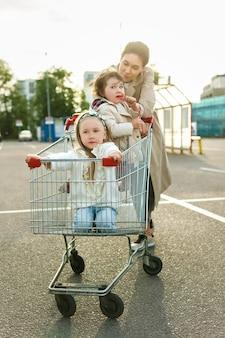 행복한 어머니와 그녀의 딸은 쇼핑 카트와 함께 재미 있습니다