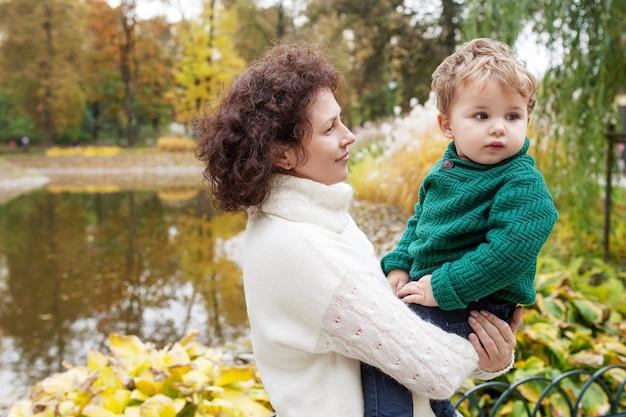 幸せな母と秋の公園で彼女の小さな男の子。母親と遊ぶ子供。抱きしめる母と息子。