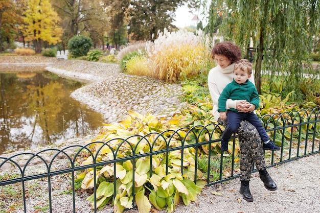 幸せな母と彼女の小さな子供公園で母親と一緒に座っているかわいい子供