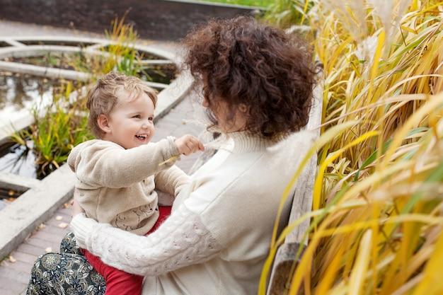 幸せな母と彼女の小さな子供。公園で母親と遊ぶ笑顔の子供。抱きしめる母と息子。