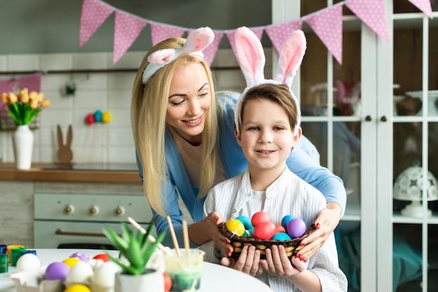 행복한 어머니와 그녀의 작은 아들은 부활절을 준비, 계란 색칠