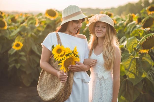 幸せな母とひまわり畑で10代の娘