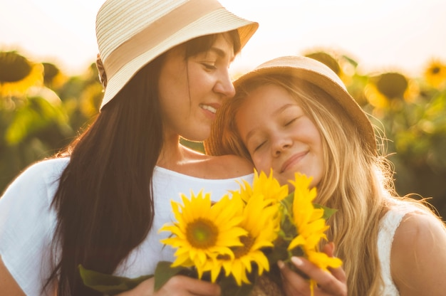 Счастливая мать и ее дочь-подросток в поле подсолнечника