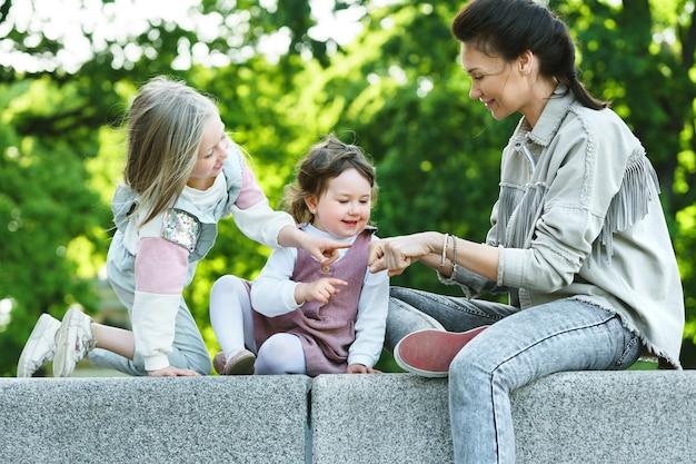 Счастливая мать и две ее дочери сидят и играют в городском парке