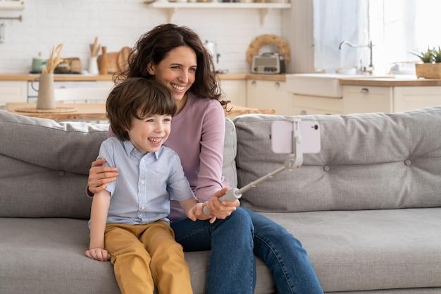 Счастливая мать и сын ребенка, держащий смартфон на селфи-палке для видеозвонка, делают совместное фото, сидя на диване у себя дома.