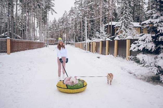 행복 한 어머니와 분홍색 따뜻한 착실히 보내다 걷는 재미에 귀여운 소녀는 눈 덮인 하얀 겨울 시골 야외에서 빨간색 시바 inu 강아지와 함께 풍선 스노우 튜브를 타고