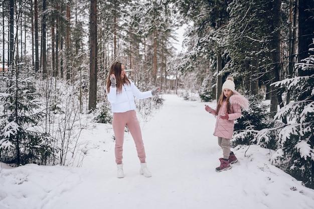 행복 한 어머니와 분홍색 따뜻한 착실히 보내다 걷는 눈싸움 재미에 귀여운 소녀