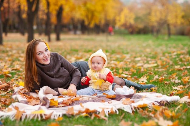 Счастливая мать и маленькая дочь играют в осенний парк.